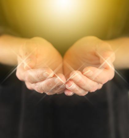 dorado: Sanador con mujeres Curación de oro del orbe de energía de la mano en posición ahuecada con un brillante orbe de la energía de oro flotando por encima y destellos alrededor puntas de los dedos