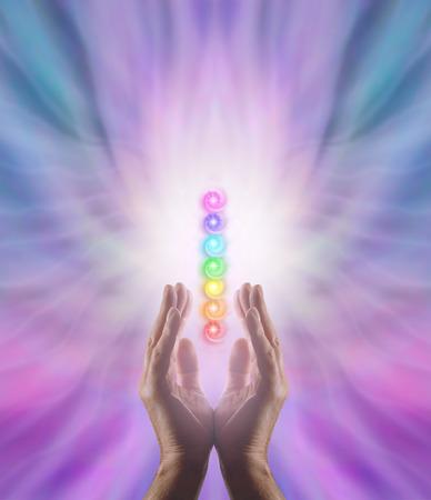 Het verzenden van Chakra Healing Energy - Mannelijke parallel handen naar boven met witte energie en de zeven chakra's zweven tussen op een roze en blauwe etherische vorming energie achtergrond Stockfoto