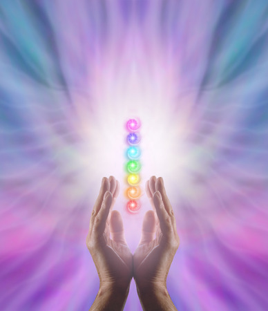 energy channels: Sending Chakra Healing Energy - Male parallel hands facing upwards with white energy and the Seven Chakras floating between on a pink and blue ethereal energy formation background