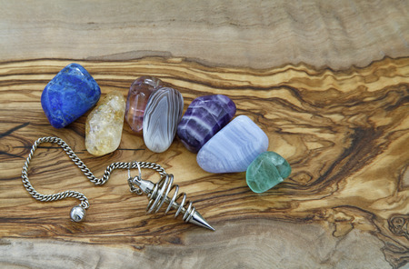 Healing Crystals and Dowsing Pendant - Selection of healing crystals and a spiral dowsing pendant arranged on a piece of flat smooth olive wood Foto de archivo
