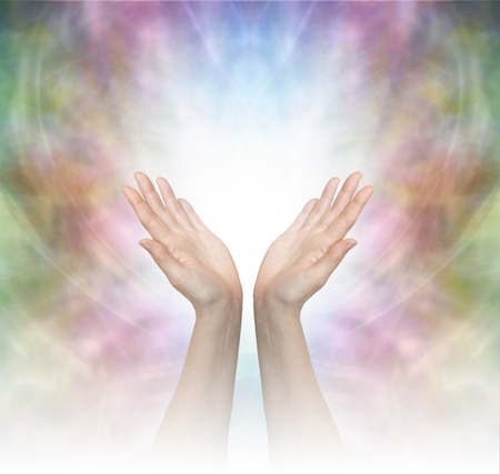 healing chi spiritual: Divine Healing Energy - Female healing hands outstretched with misty white graduated light on a beautiful delicate multicolored energy field background