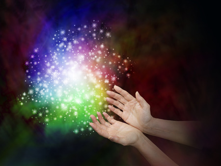 reiki: Magic Dust - Female hands reaching towards a cloud of rainbow colored sparkles on a dark background with copy space