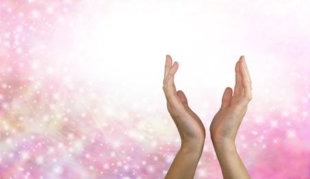 치유 에너지를 보내기 - 여성 치유의 손이 분홍색 반짝 에너지 배경에서 도달
