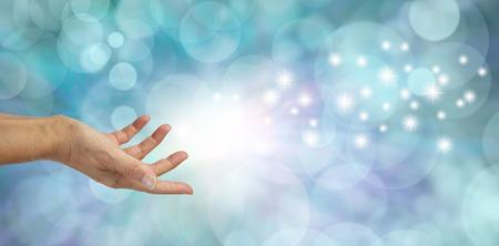 Magical Moment - Vrouwelijke hand lijkt te gooien witte glinsterende sparkles over een mooie blauwe bokeh achtergrond met veel ruimte kopie Stockfoto
