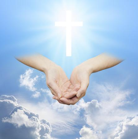 manos abiertas: Adorar a la Fuente Divina de Amor y Luz - Mujeres manos ahuecadas con una cruz blanca que brilla flotando por encima en un cielo azul durante el día soleado con nubes esponjosas Foto de archivo