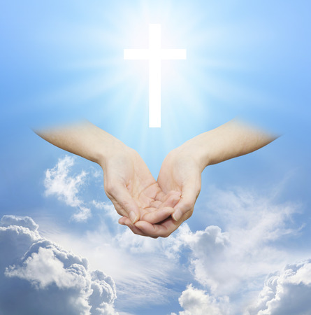praying at church: Worshiping the Divine Source of Love and Light - Female hands cupped with a shining white cross hovering above on a sunny blue daytime sky with fluffy clouds