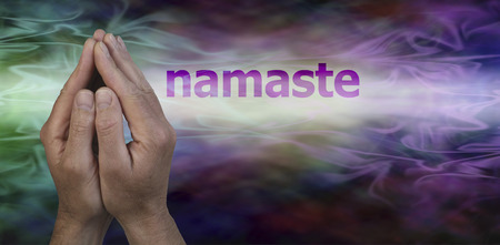healer: Namaste Greeting Website Header - Male hands in prayer position with the word Namaste floating to the right on a multi colored streaming misty graduated background with plenty of copy space beneath