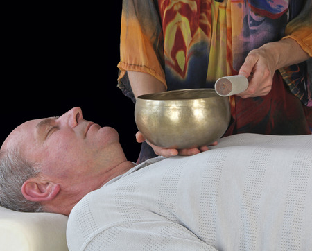 Sound Healer working with Tibetan Singing Bowl - Male patient lying supine with a female sound therapist standing at his shoulder resting a Tibetan singing bowl on his heart chakra