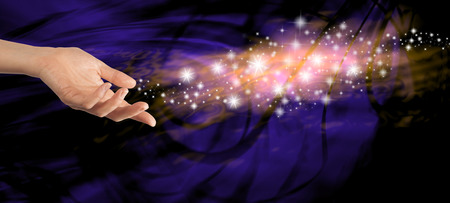 Sending out special energy - Female hand outstretched with a stream of sparkles  floating away on a dark blue swirling background
