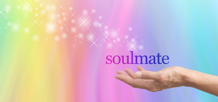 soul mate: Seeking a Soulmate - female hand palm up with the word Soulmate floating above, with a stream of glittering sparkles floating away on a rainbow colored background with plenty of copy space Stock Photo