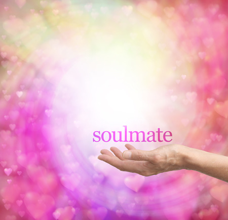 soul mate: Seeking a soulmate - female hand palm up with the word Soulmate floating above, surrounded by a spiral of pastel colored soft focus love hearts on a bokeh background