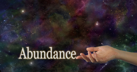 Universal Abundance - Female hand facing up with the word Abundance touching the index finger on a deep space night sky background providing plenty of copy space above