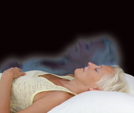 astral: Female Astral Projection Experience  - Female lying supine with eyes closed experiencing astral projection on dark background showing  soul separating from body Stock Photo