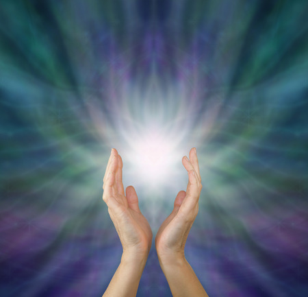 Sensing  Healing Energy - Female healing hands reaching up to white light emerging from radiating green and purple ethereal energy formation background with copy space above.