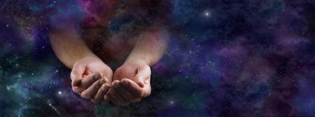 Onze Overvloedige Universe - Mannelijke handen die uit een brede donkere diepe ruimte achtergrond gebaren met cupped handen Stockfoto