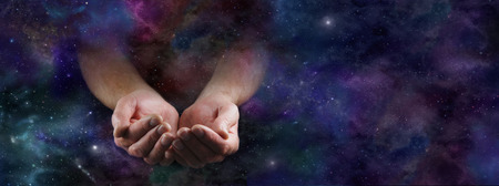wealth: Our Abundant Universe - Male hands emerging from a wide dark deep space background gesturing with cupped hands