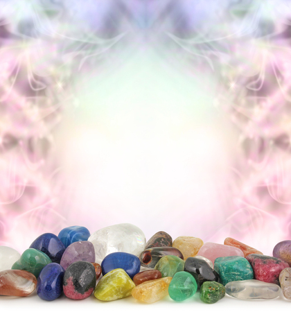 gems: Healing Crystals Border - Decoractive pastel colored border frame background with a selection of multicolored tumbled healing crystals at the front and plenty of copy space above