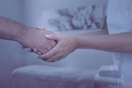 cool colors: Therapist welcoming new patient - Female therapist holding hand of male client greeting him into therapy room with muted cool colors and soft focus background