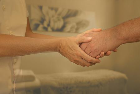 colores calidos: Terapeuta acogedor paciente nuevo - Mujer terapeuta de la mano del cliente masculino saludándolo en sala de terapia con colores cálidos apagados y fondo suave del foco Foto de archivo
