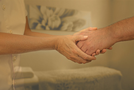 Therapist welcoming new patient - Female therapist holding hand of male client greeting him into therapy room with muted warm  colors and soft focus background