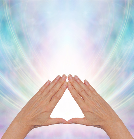 Pyramid Power Energy Healing - female hands making a triangle shape on a misty blue flowing triangular shaped energy field with plenty of copy space above