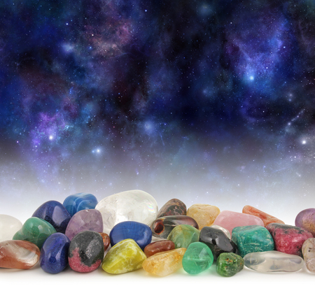 crystals: Cosmic Healing Crystals - Deep space background with stars, suns and planets with a selection of multicolored tumbled healing crystals at the front and plenty of copy space above