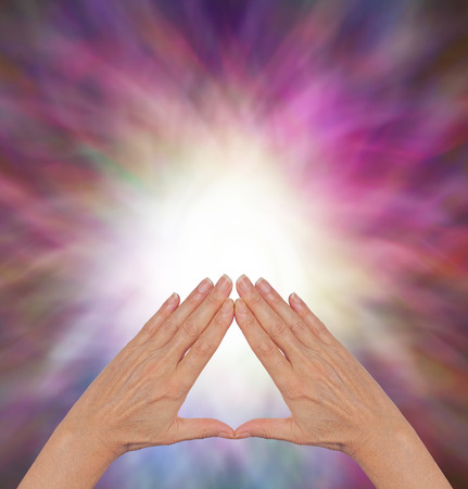 resonate: The Power of Pyramid Healing - female hands making a triangle shape on a flowing triangular shaped energy field with plenty of copy space