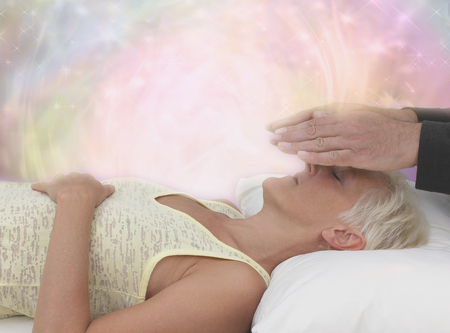 Channeling Healing Energy - Female patient lying with eyes closed and male healer with hands hovering channeling energy with misty sparkling pink energy field all around