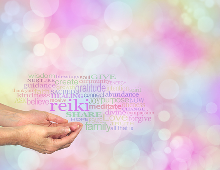 spiritual energy: Reiki Share - Female hands cupped with the word Reiki floating above, surrounded by a relevant healing word cloud on a pastel colored bokeh background Stock Photo