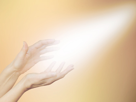 healing chi spiritual: Beautiful Golden Healing Energy  -    Female healing hands outstretched with bright shaft of light beaming out and up on a pale golden background