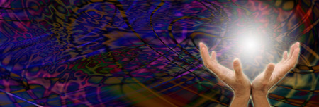 Orb Energy - Female healer with cupped hands sensing a ball of white light on a multi colored wide dark psychedelic energy formation background with copy space on left hand side