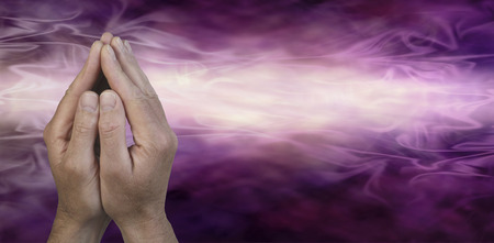 Cupped Hands in Prayer Position -  Male hands cupped together in prayer position on a dark purple and light pink energy streaming misty graduated background with plenty of copy space on the right hand side Stock Photo
