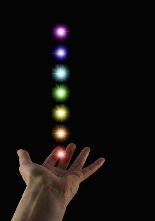 qi: The Seven Chakras -  female healers hand  palm up with a stack of seven rainbow colored chakra starbursts floating above on a black background Stock Photo