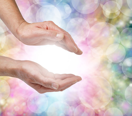 Beautiful Healing Energy - Male hands facing each other palm up with a ball of white light between on a multicolored rainbow bokeh background