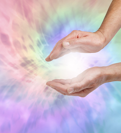 color healing: Beautiful Angel healing energy  -    Male spiritual healer with outstretched cupped hands working with a vortex of rainbow colored energy Stock Photo
