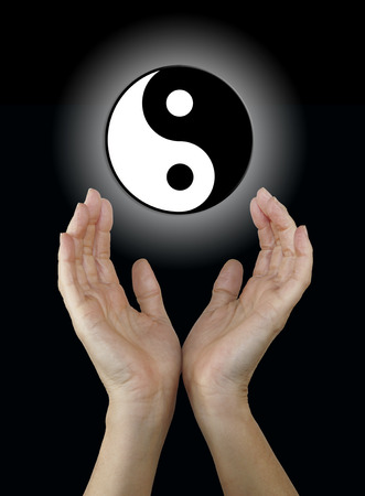 reaching up: Yin and Yang Symbol - Female hands reaching up towards a floating black and white yin yang symbol on a black background