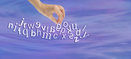 dyslexic: Pinpointing Dyslexia Website Banner -  female hand picking out a reversed G from a jumble of alphabet letters flowing across the  page symbolizing dyslexia Stock Photo