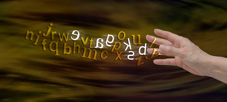 erratic: Understanding Dyslexia Website Banner -  female hand with the alphabet flowing from fingers in gold with six letters flipped in white to symbolize dyslexia Stock Photo
