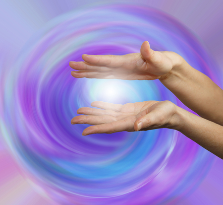 healing energy healer: Vortex Healing Energy -  Parallel female hands with ball of white light between on a purple pink blue spiraling vortex energy field background