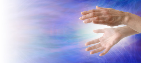 distant healing: Sending Healing Energy  - Pair of female hand with energy between sending towards the light on left hand side, on a blue energy formation background with plenty of copy space Stock Photo