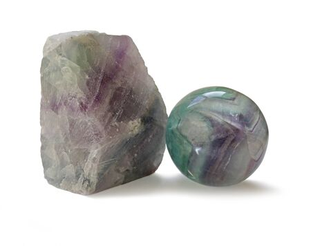 crystal therapy: Polished and rough natural specimens of Flourite banded crystal - two different specimens of fluorite, one chunk unpolished and one shaped and polished on white background