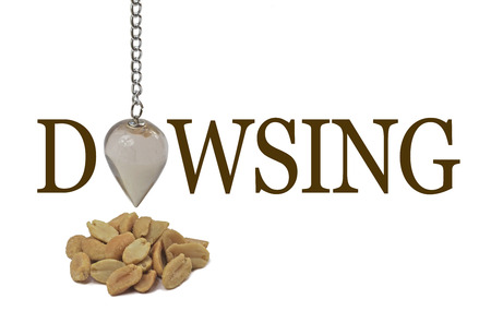 divining: Dowsing for a peanut allergy - a dangling quartz pendulum making the O of DOWSING over a small pile of peanuts on a white background