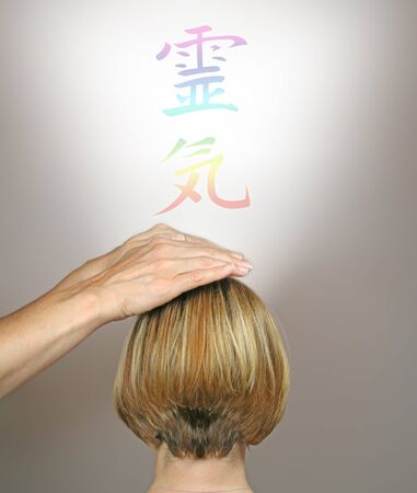 Channeling Healing through Crown Chakra - female healer channeling healing energy through female clients chakra with a rainbow colored Reiki Kanji symbol floating above on a neutral background Stock Photo