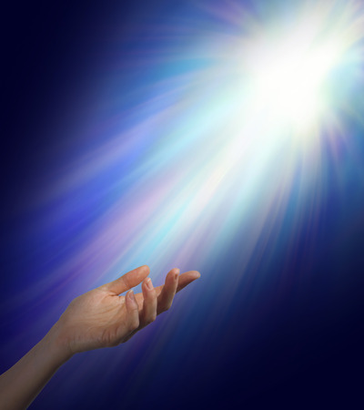 spiritual background: Seeking Spiritual Guidance    Female hand reaching upwards into a bright energy burst  with subtle rainbow color strands with plenty of copy space