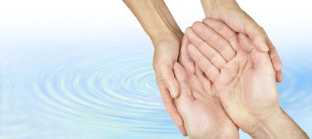 manos limpias: Campaña Water Aid - manos femeninas sosteniendo suavemente manos de los hombres en la posición ahuecada sobre un fondo ondulación del agua azul decoloración a blanco con un montón de espacio de la copia