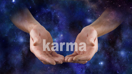 universal enlightenment: Cosmic Karma is in Your Hands  - Male hands emerging from a deep space night sky dark blue  background, cupped cradling the word KARMA