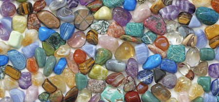 stones: Multicolored tumbled crystal stones background - a large quantity of different colored healing tumbled gem stones making up a backdrop for use as a background