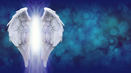 ali angelo: Ali di angelo su Blue Bokeh Banner - Ampio sfondo blu bokeh con un grosso paio di ali d'angelo sulla sinistra e un fascio di luce brillante tra Archivio Fotografico