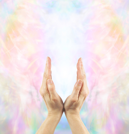 healing energy healer: Channeling Angelic Healing Energy - Pair of female hands cupped upwards with a beautiful ethereal angelic energy field and white light Stock Photo