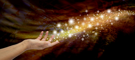 intention: Creating Magic - Female open hand appearing to send out a stream of sparkles and glitter on a golden and black flowing background